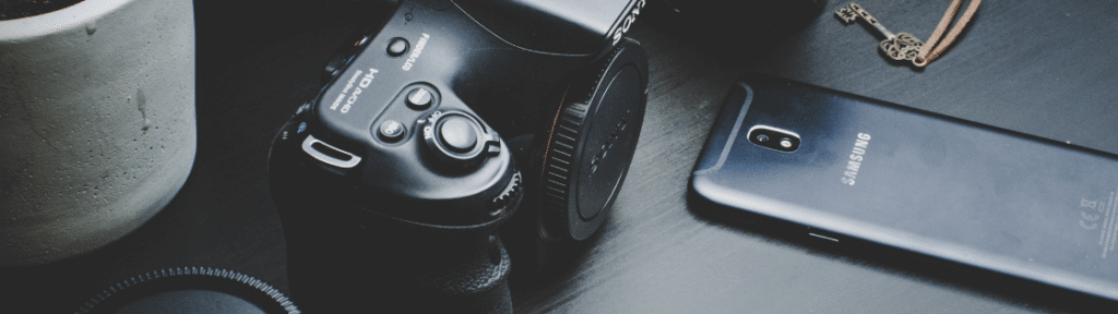 Sony SLR camera with no lens attached and Samsung smartphone lying face down